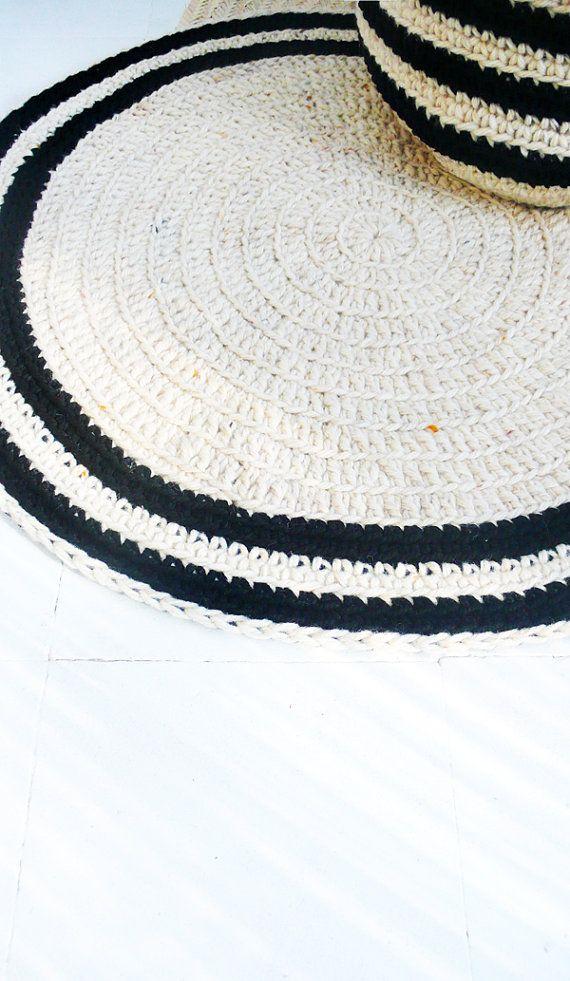 Laine crochet dépaisseur de rond tapis sol - naturels non teint et noirs rayures   Tapis faits avec de la laine épaisse, le résultat est un point énorme avec du volume et de légères variations dépaisseur, ce qui donne un rustique et naturel.  100 % laine incolores, du Moyen Atlas du Maroc.  diamètre : 80 cm. Couleur : Écru avec des bandes noires  Matière : Laine teinte et coton noir    Fabriqué dans un environnement sans animaux et sans fumée.  Toute la main bonneterie et main tricot points…