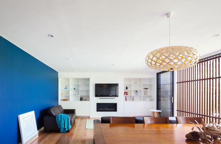 Living room with blue wall and timber screen — design by Bijl Architecture