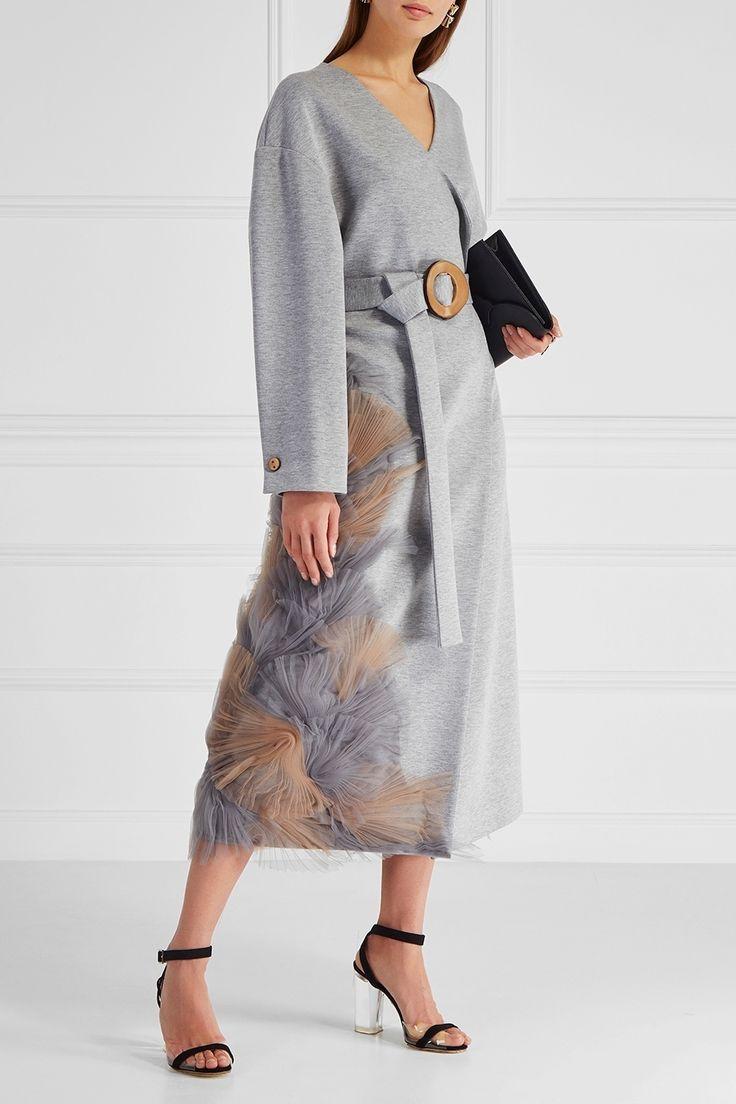 Серое пальто oversize-кроя из коллекции FW 17/18 российского бренда Ruban. Модель выполнена в характерном для марки лаконичном стиле. Глубокий V-вырез без воротника, распашные полочки, которые фиксируются широким поясом с пряжкой, и спущенная линия плеча. Декор в виде плиссированной сетки сбоку завершает дизайн пальто.