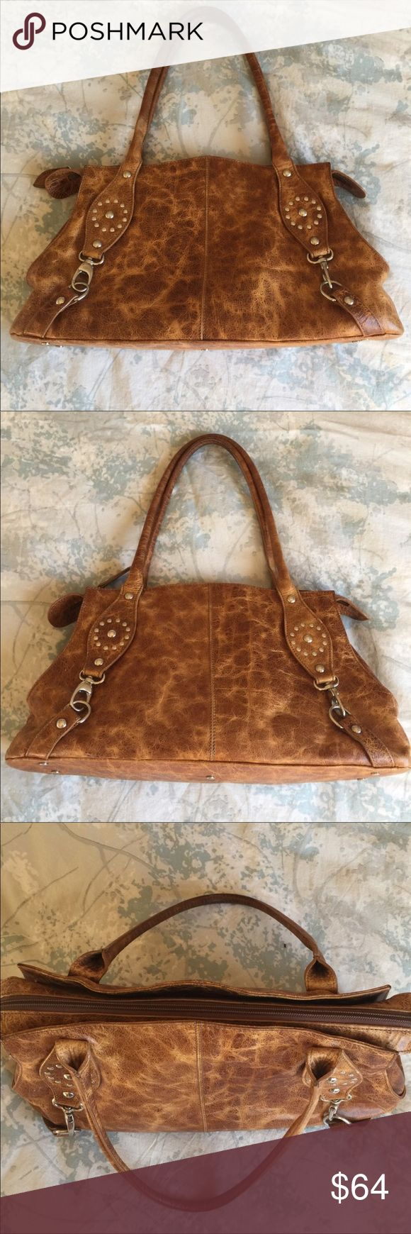 """Roberta Gandolfi Italian brown leather handbag Roberta Gandolfi Italian brown leather handbag.  Gorgeous handbag in distressed medium tone brown leather with silver detail design.  Silver feet on the bottom this protect the bag, nice medium size and vey versatile.  Wear hand held or over the shoulder, top zipper closure.  EUC Measurements approximately 17"""" long 9.5 height 4"""" depth. 9"""" handle drop. Minimal wear on the inside and out. Inside - one zipper pocket and two small pocket. Roberta…"""
