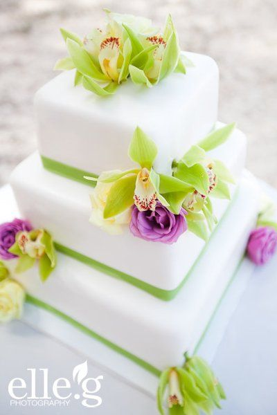 Simple and elegant three-tier, square wedding cake with green orchids and pale purple mini-roses.