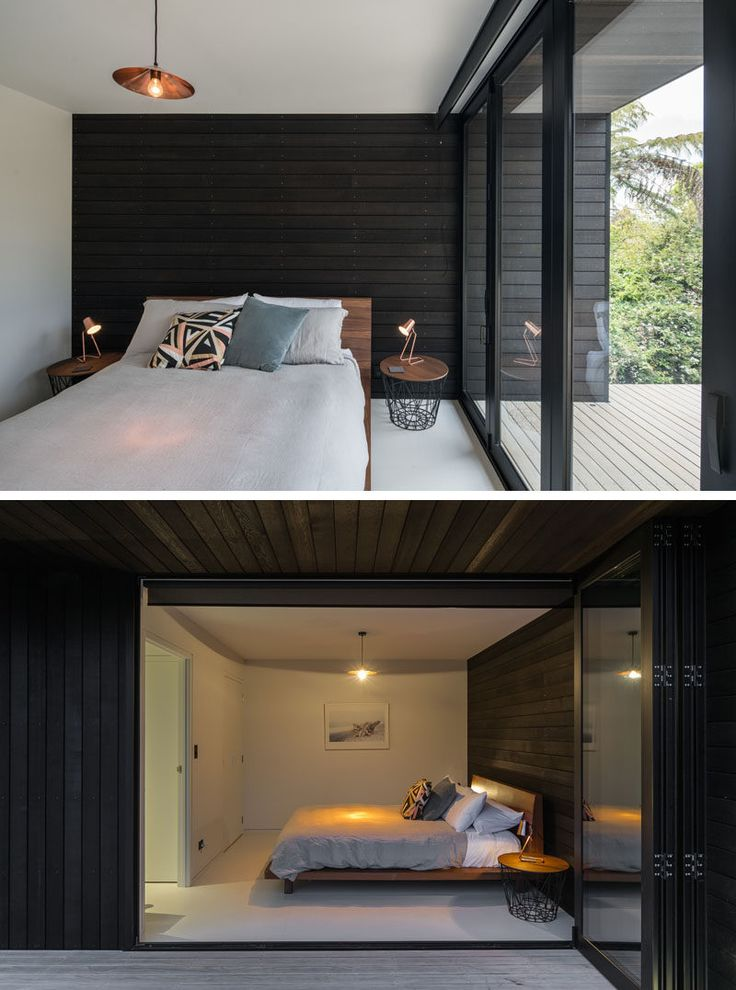 This modern bedroom has an accent wall of black wood that continues through to the exterior of the house.