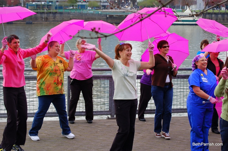 All of these women are Breast Cancer Survivors.  They are wearing pink gloves from Medline and holding pink umbrellas in the making of a video on the Portland, Oregon waterfront. The video is called The Pink Glove Dance the Sequel and can be seen on youtube.