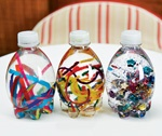 Insert craft items in bottle, fill with water leaving a 1 inch space, and secure top with hot glue- let dry for 5 mins and voila!