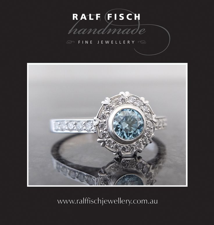 18ct white gold hand crafted cluster engagement ring with an 'Ice Blue' centre diamond, framed by smaller round brilliant cut diamonds. The giver of this ring came to us with a fantastic theme for the design of this ring, which inspired us to suggest using an unusual centre diamond and adding unique details to the cluster setting. We like to think we took a passion and turned it into a wearable work of art!
