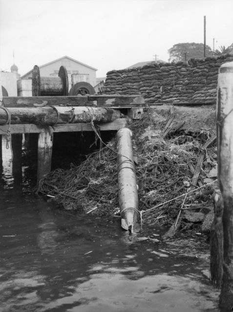 Japanese Type 98 torpedo that ran aground on Green Island in Sydney Harbor during the submarine attack 9 days earlier being prepared for recovery, Sydney, Australia, Jun 10, 1942. Note the sandbags.