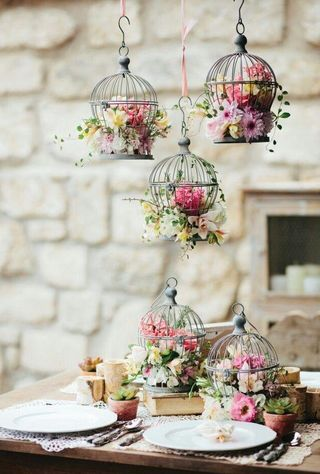 Great idea using bird cage for flower arrangement.