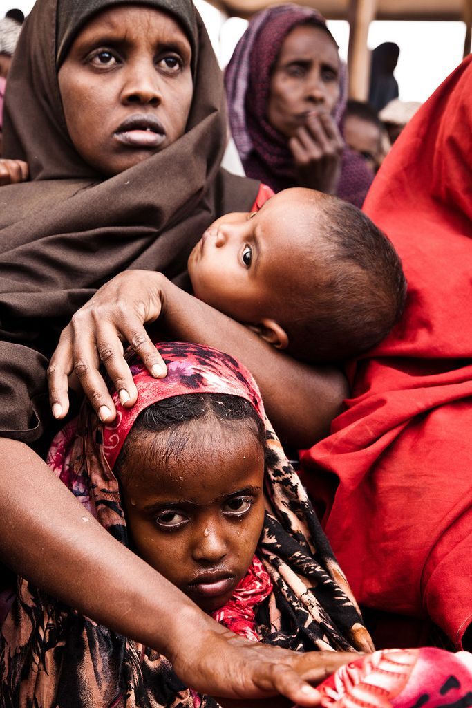 A Somali refugee woman cradles her baby after dousing her elder daughter with water to keep cool under the sweltering sun. ©