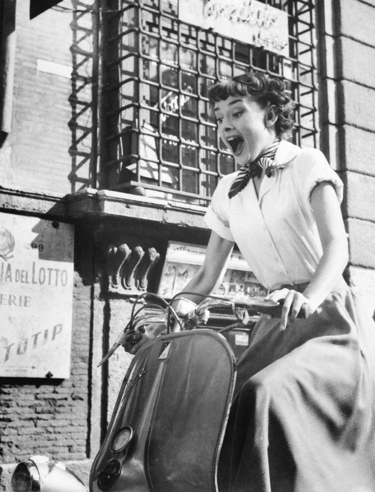 "Audrey Hepburn riding a Vespa in the 1953 film ""Roman Holiday"" with Gregory Peck:"