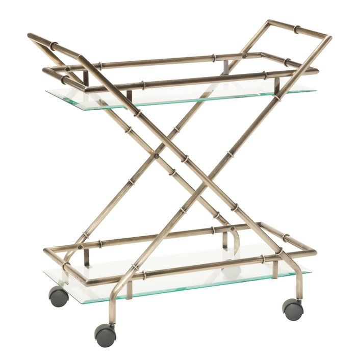The Lanai serving cart beautifully fashions together clean, symmetrical lines, stylish aesthetic, and a hint of distinctively organic influence. Look no further for the perfect match to any home environment, whether it's an elegant, enriching traditional atmosphere or a quirky, eclectic, and spirited aura. Crafted of an antique brass finish metal that is made to visually replicate the natural qualities of bamboo. The clear tempered glass surface tray is framed by metal bars that criss-cro...