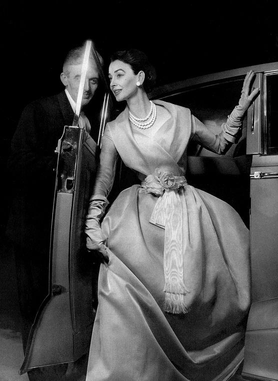 Dorian Leigh is wearing a pale blue organdy Marie-Antoinette style evening gown, which has a fichu collar and a white moiré sash, by Christian Dior, 1955.