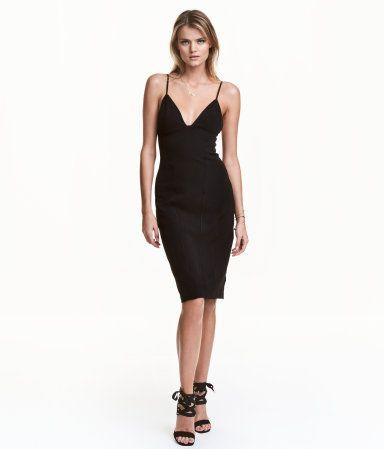 Sort. En knelang, figursydd kjole i elastisk, vevd kvalitet. Kjolen har smale, regulerbare skulderbånd og er avskåret under bysten. Zick zack-sømmer foran