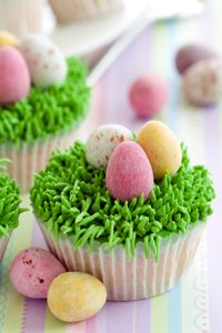 Easter cupcake decorating ideas. Use frosting or shaved coconut dyed green as Easter grass for cupcake toppings. Top with candy eggs.