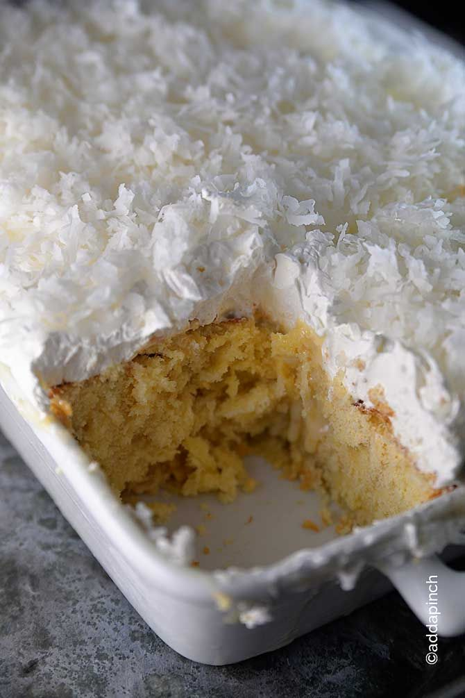 The Ultimate Coconut #Cake Recipe from addapinch.com Made with coconut cream, coconut milk, coconut whipped cream and topped with coconut flake!