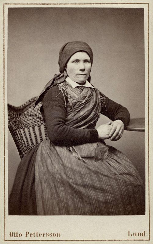 Kvinna poserar sittande i en sockendräkt, Löddeköpinge, Harjagers härad i Skåne - Nordiska Museet - NMA.0042841 - Svenska folkdräkter – Wikipedia. Otto Petterssons fotografiska ateljé