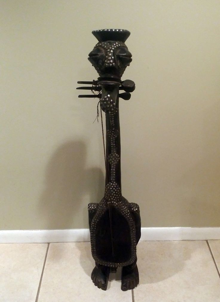 "This African instrument is from Kenya and carved from wood. It is a fantasy piece that resembles a guitar or harp. It is 43"" tall, has three tuning pegs, strings and is decorated with silver nail heads. It is an unique sculpture/instrument and sure to be a great addition to any African art collection."