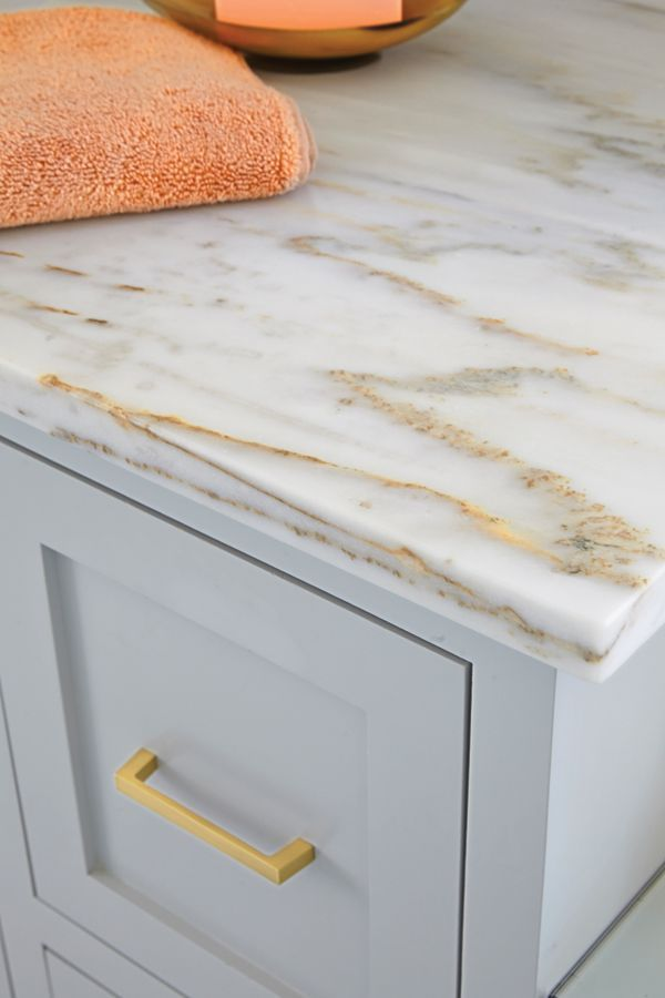 Marble countertops with specks of gold mesh beautifully with brass fixtures.
