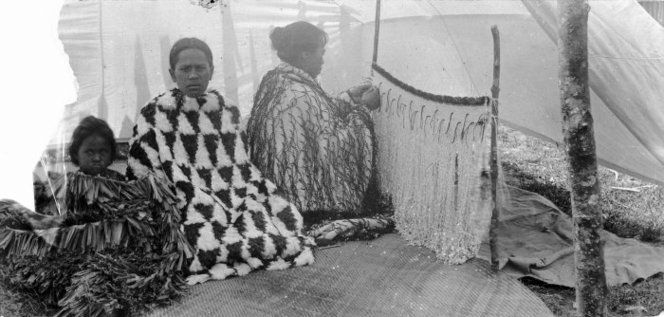 Unidentified Maori woman, girl and child, with cloaks. From left to right: a flax cloak, kahu huruhuru (feather cloak) and korowai (tag cloak). The women on the right is in the process of making a korowai.