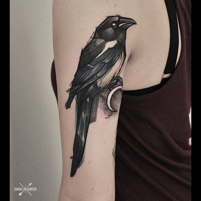 Sketchy magpie tattoo on the back of the left arm.