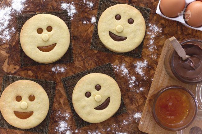 Le faccine di frolla con cioccolato e marmellata sono sagome di soffice e friabile pasta frolla farcite con Nutella e marmellata ideali per merenda.