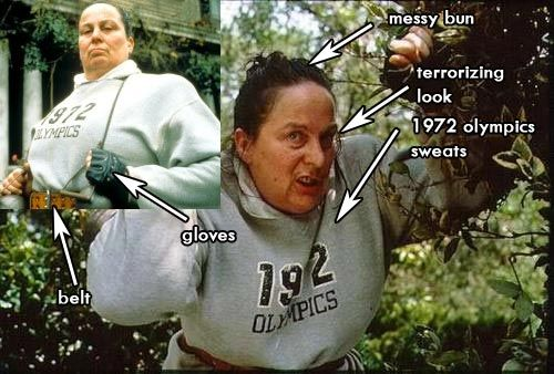 Ms. Trunchbull in sweats from Matilda, the movie - grey hoodie, grey sweatpants, wide leather belt, weightlifting gloves, hair in a tight bun, a ferocious frown.