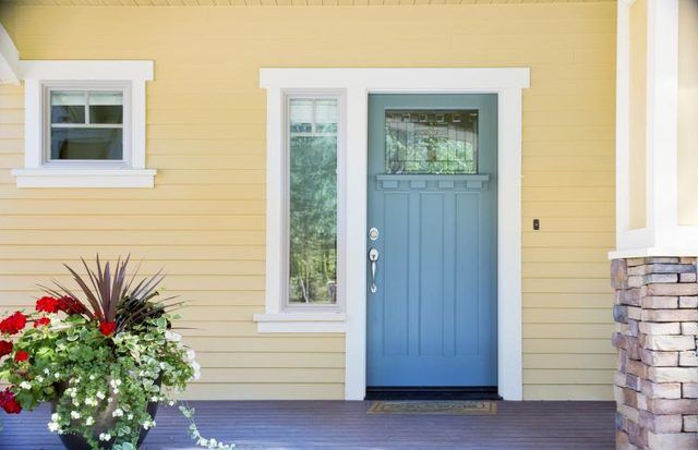 This door is easily spotted with the white frame and the soft yellow siding