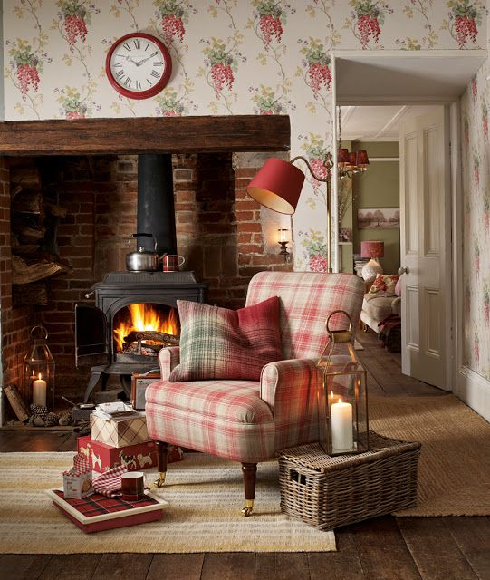 Pretty wisteria wallpaper decorates the walls of this cosy English cottage living room with woodburner and comfy Welsh blanket covered armchair