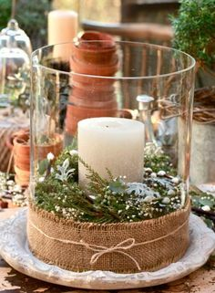 Love this simple idea... dress up a small hurricane with a bit of burlap, lace or other material (a dab of hot glue should do the trick), add some greenery, small flowers, or herbs (such as cinnamon sticks) to the outer interior walls and place a small candle in the center!!