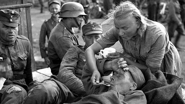 A Finnish Lotta volunteer nurse-aid tends to a wounded Finnish soldier in Karelia during the ongoing Finnish-Soviet Continuation War. August 1941.