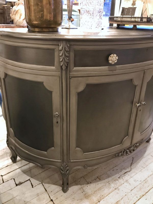 Custom Painted Demilune SPH756: For this demilune cabinet, we used Smoke Metallic Paint to add some extra shine to this beauty. We started with a base coat of French Linen Chalk Paint by Annie Sloan, then applied the metallic paint to the panels. The chalk paint acts as a primer to help the metallic paint adhere. To finish and protect the piece we used clear and black wax everywhere EXCEPT the metallic panels, where we used General Finishes High Performance Top Coat in Satin finish instead.