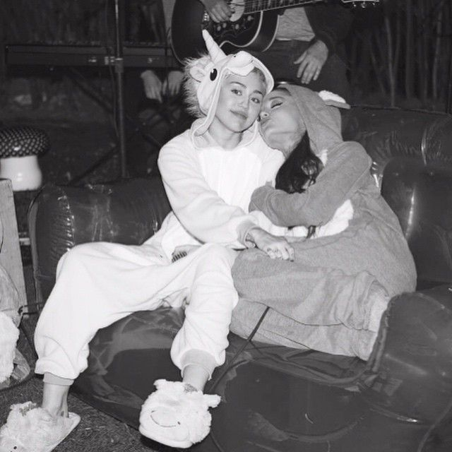 """They may be in ridiculous onesies and sitting on an inflatable couch, but Ariana Grande and Miley Cyrus are seriously singing in this latest edition of Happy Hippie Presents: Backyard Sessions. The pop stars cover Crowded House's 1986 hit, """"Don't Dream It's Over,"""" and their voices seem made for each other. Cyrus, 22, and Grande, 21, recorded the song with a band in the former Hannah Montana star's own backyard (hence the name of the sessions). PHOTOS: Most Memorable Stage Styles Happy Hippie…"""