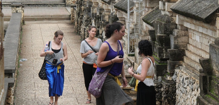 These visitors enjoy a cultural adventure as they wrap themselves in a Balinese sheet and venture inside a sacred temple