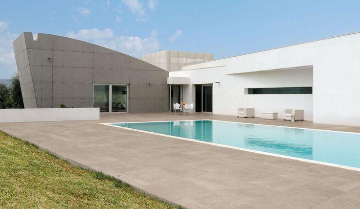 Modern huis met zwembad. Tegels zijn grote tuintegels van 60x60 cm.