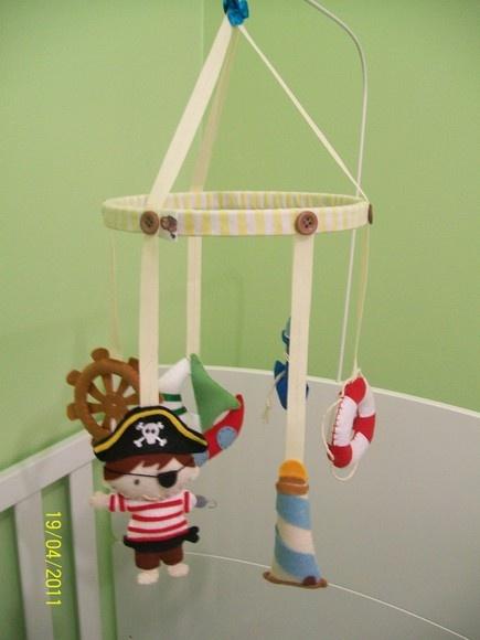 Móbile em feltro. Modelo Pirata. Aro em madeira forrado com tecido em algodão. Itens: 6 peças: barco, bóia, farol, leme, menino pirata e âncora Favor verificar cores e estampas disponíveis. Faço outros modelos e cores. Fica a sua escolha.  PROMOÇÃO!! FRETE GRÁTIS (VIA PAC) NAS COMPRAS ACIMA DE R$100,00 (VÁLIDO SOMENTE PARA PAGAMENTO EM DEPÓSITO EM CONTA) FRETE GRÁTIS NÃO É VÁLIDO PARA PAGAMENTOS COM PAG SEGURO!!! R$45,00