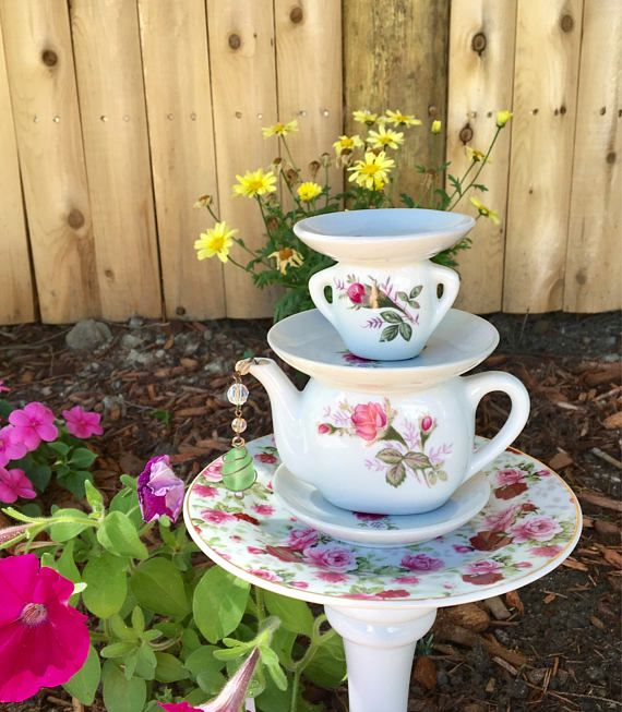 Whimsical unique tea pot garden stake featuring an upcycled children's tea set in pink and white.  A fun addition to your garden and yard!