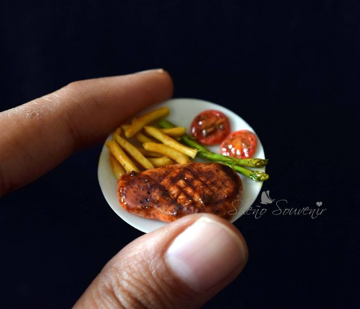 Miniature beef steak with fries, asparagus and grilled tomatoes.