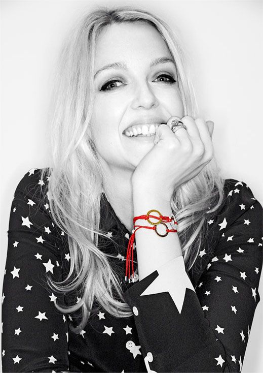Lauren Laverne shows off her red/orange Fashion Targets Breast Cancer bracelets. They really stand out against the black and white photograph!