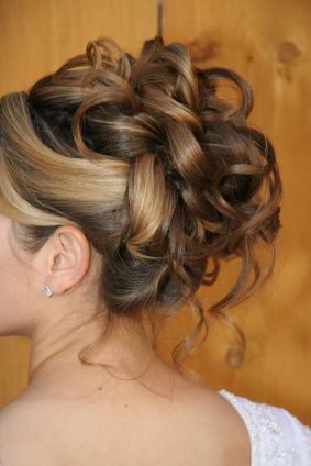 This updo is lovely and sports large rings of curls done in defined sections with loose strands left out to hang naturally.  This is a good choice for a bride or would be fabulous for a school dance. The blonde highlights stand out here with this light brown color. More on Formal Updo Big Loose Curls