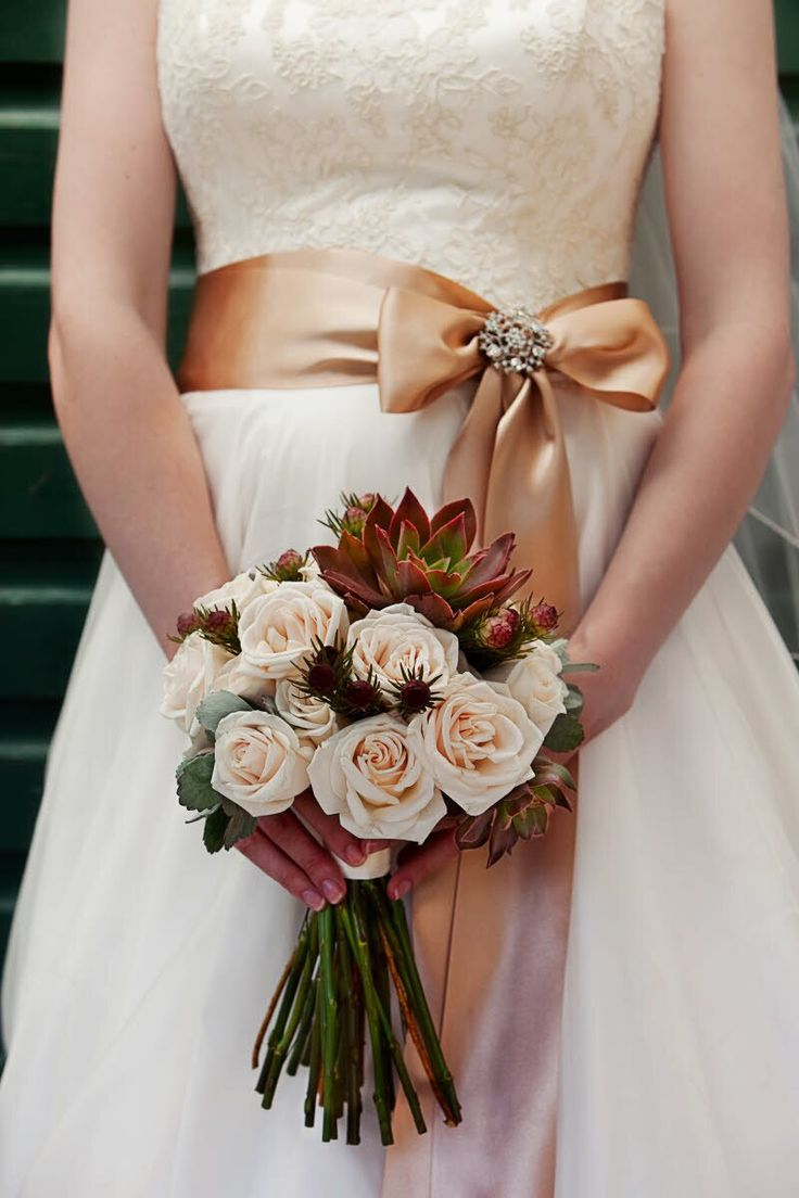 Bride wearing ivory and white wedding dress with golden-orange sash holding a bouquet of ivory roses with maroon and dark green accents - photo by South Africa based wedding photographer Greg Lumley