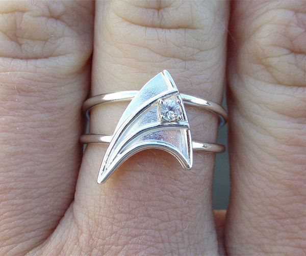Hey Trekkies...are you looking for a cute ring? This custom Starfleet insignia ring comes from Etsy artist Valerie of VaLa Jewellery. It's made of sterling silver and gold and contains a small white sapphire. It cost s $500(USD). Hey, geek love is priceless. What's $500(USD) – especially in Federation Credits?