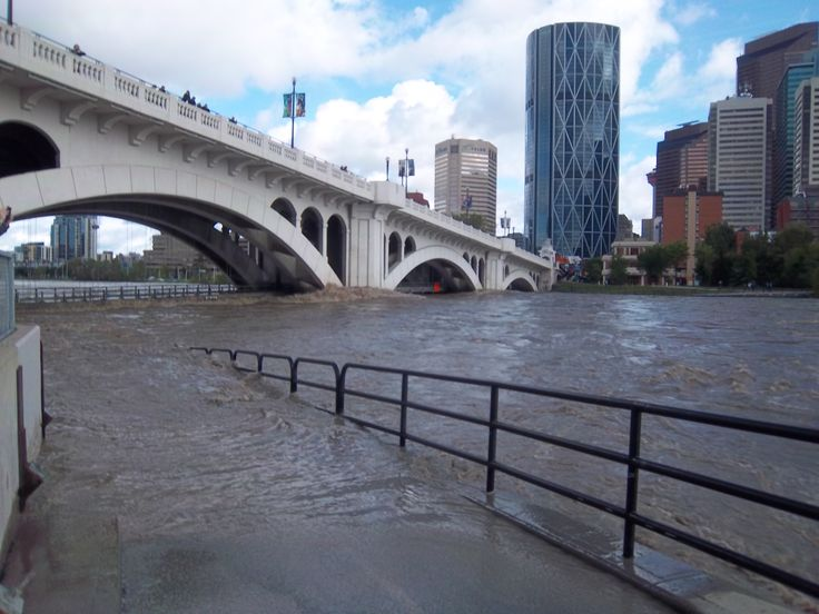 "Centre St. Bridge over bow river during Calgary flood. The ""Bow"" Calgary's tallest building in the background."