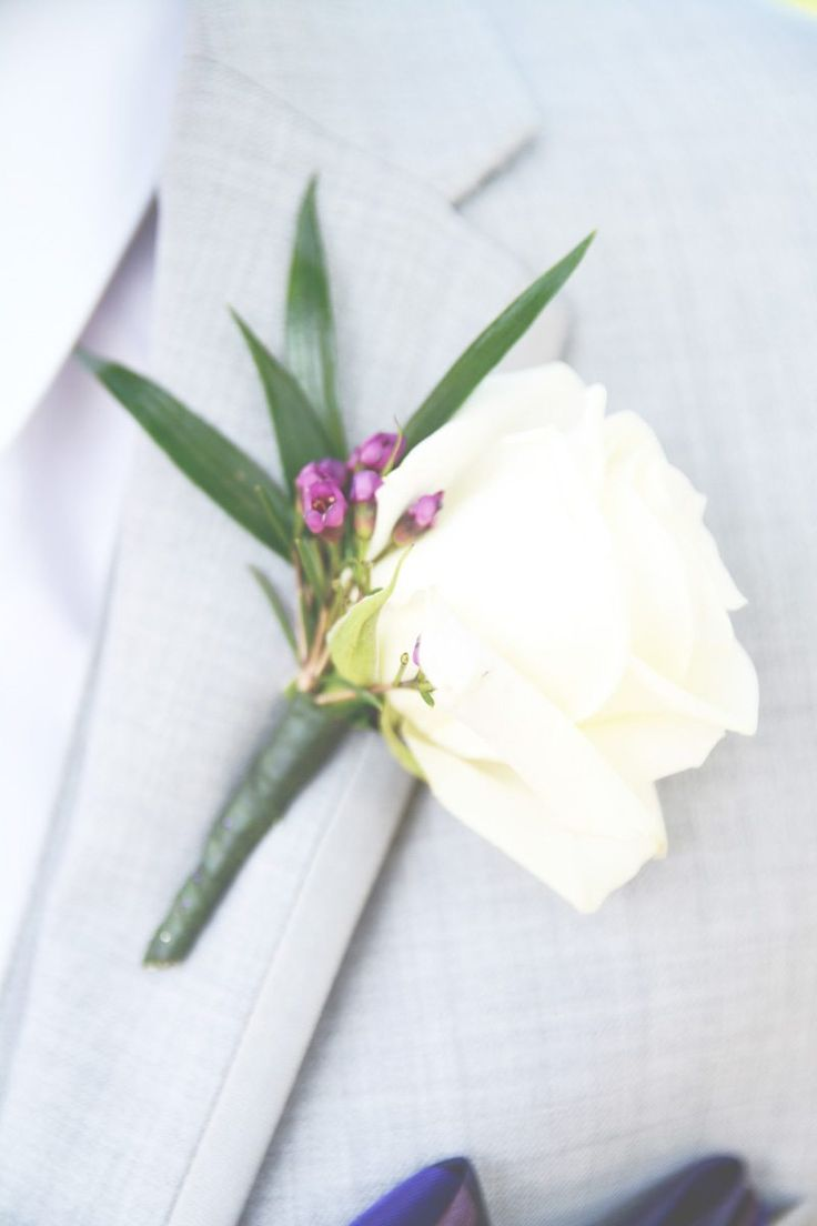 Simple white rose boutonniere with light accents https://www.thecelebrationsociety.com/weddings/purple-outdoor-wedding-mountain-laurel-farm-cleveland-ga/