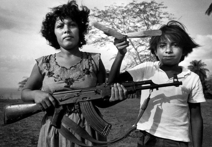 ©Larry Towell – Magnum Photos – A woman and child train with a local defence militia against invading Contras, the U.S.-backed counter-revolutionaries. Nicaragua. Solentiname Islands. 1984.
