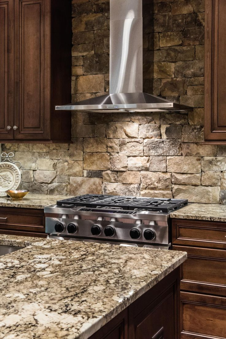 A stainless steel range hood is a sleek, contemporary counterpoint to the stacked stone backsplash.