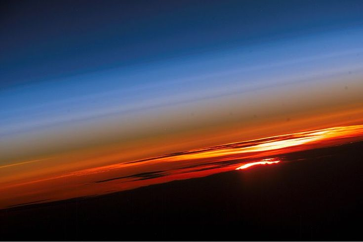 This photograph from astronauts on board the orbiting International Space Station (ISS) shows the Earth's limb, or horizon line, at sunset. Sunsets are relatively common sights for astronauts on board the ISS—they can be seen up to sixteen times each day.