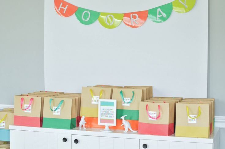 Dinosaur themed third birthday party with store-bought and budget-friendly decorations and food. Dinosaur party favors.