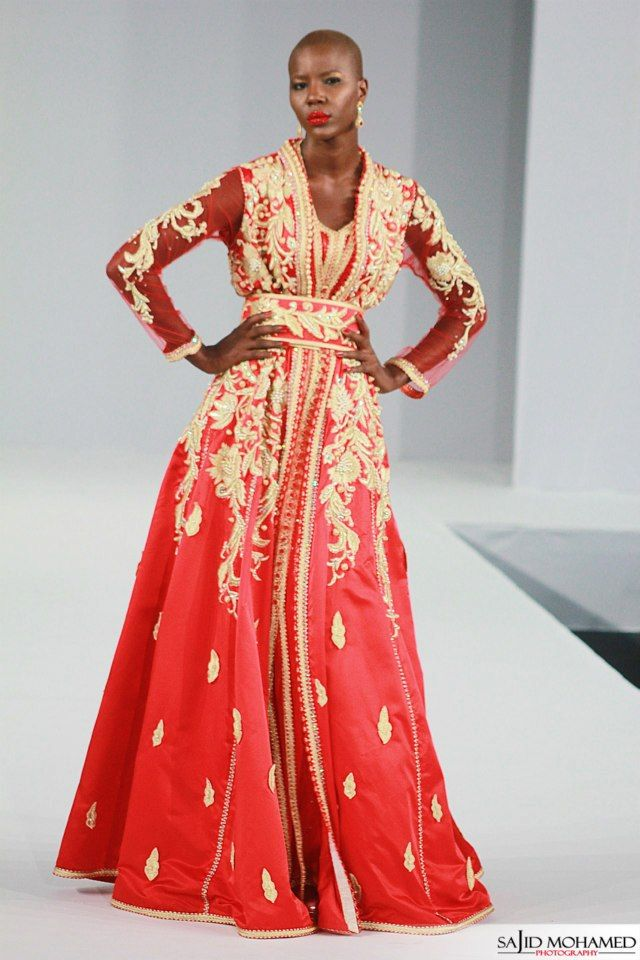 Model Keina Diouf in a red silk caftan with gold silk embroidery on the silk chiffon overdress.