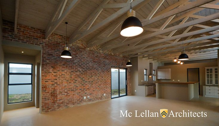 rough bagwashed brick wall stained cement floor and whitewashed exposed beams trusses