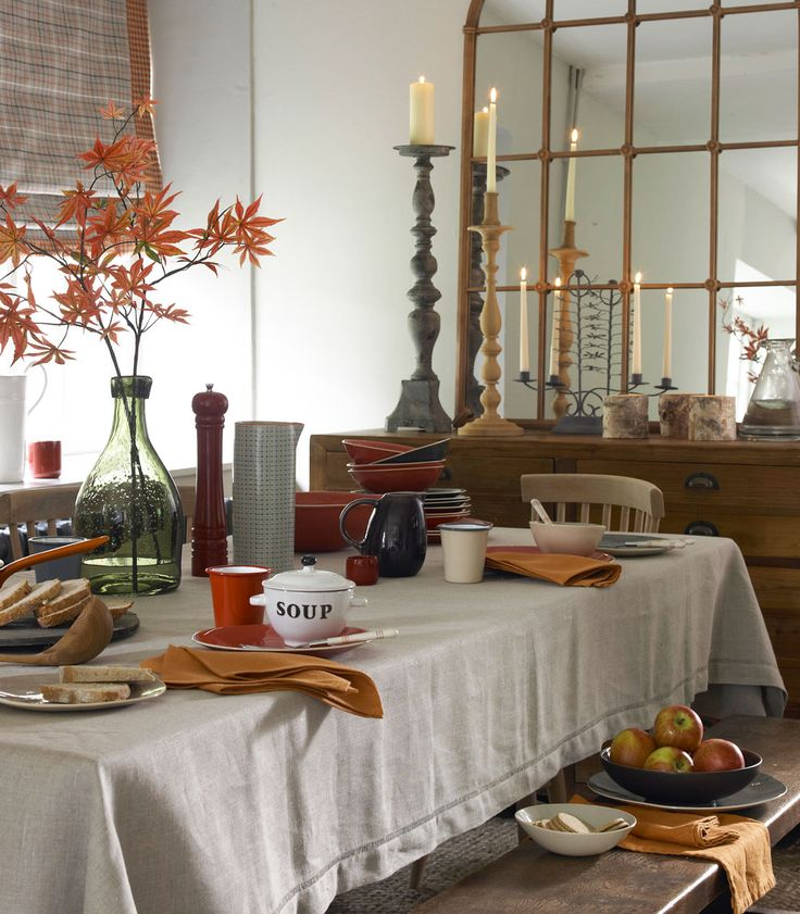 Add an atmospheric glow at suppertime with candle flames reflected in an oversized mirror. Close the door on those first frosts and settle down for a hearty meal surrounded by freshly gathered leaves in an autumnal palette of oranges and red hues. Display simple white candles in carved wooden holders and position in front of a mirror to multiply the shimmering effect and boosting light levels.