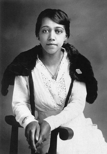 Young African American woman seated wearing a white cotton blouse and skirt with a dark fur stole around her shoulders. c1915
